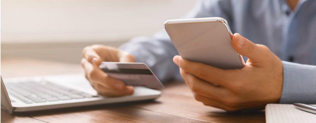 Händer håller i mobil och betalkort vid dator